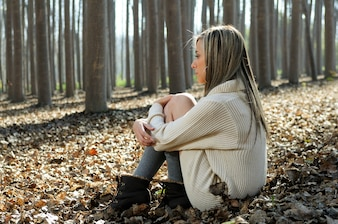 Blonde woman sitting on leaves in a forest