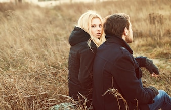 Blonde woman sitting with her partner on the meadow