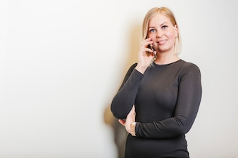 Blonde woman standing holding phone