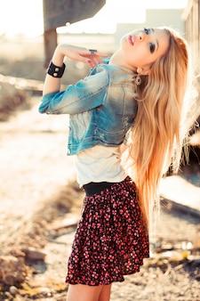 Blonde woman wearing skirt and denim jacket