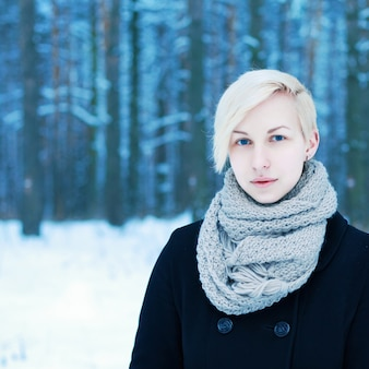 Blonde woman with scarf and black coat in the snow