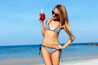 Blonde woman with striped bikini posing with her drink