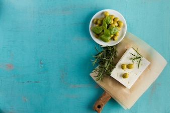 Blue background with olives, cheese and aromatic herb