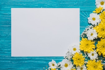 Blue background with piece of paper and decorative flowers