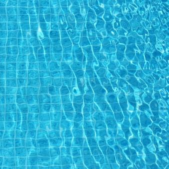 スイミングプールで青い波紋のある水の背景