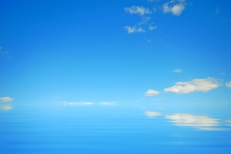 Blue sky with clouds reflected in water