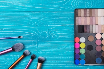 Blue surface with powders and make-up brushes