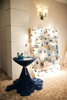 Blue table stands before wall with photos and lights