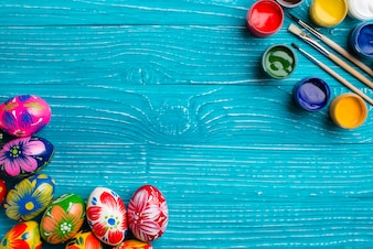 Blue wooden background with easter eggs and paint jars