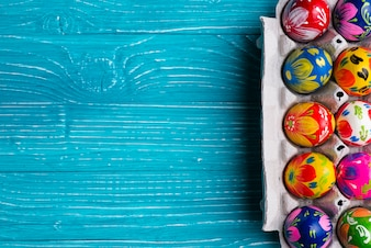 Blue wooden background with easter eggs on egg box