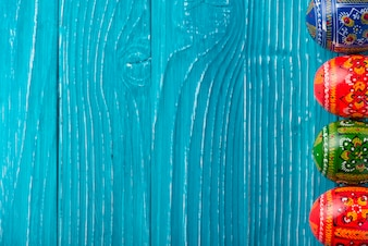 Blue wooden background with easter eggs