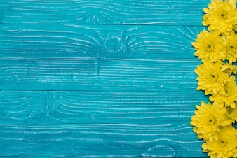 Blue wooden background with flowers and space for messages