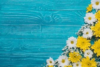 Blue wooden background with yellos and white flowers