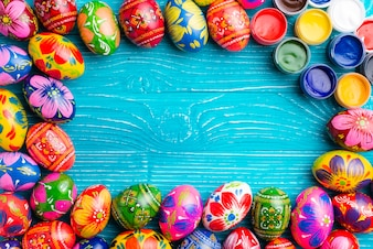 Blue wooden surface with easter eggs and paint jars