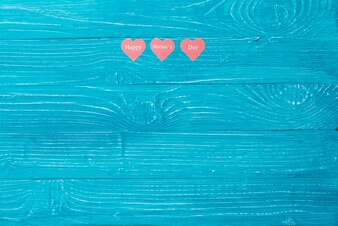 Blue wooden surface with three paper hearts and blank space