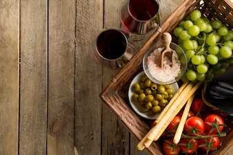 Boards with wine glasses and basket full of healthy products