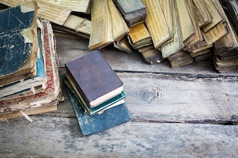 Books piled up on a wooden floor