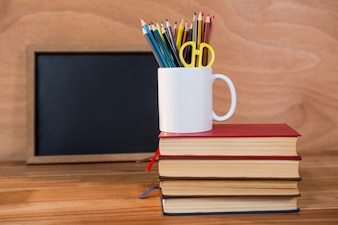 Books stack with colored pencil on a mug