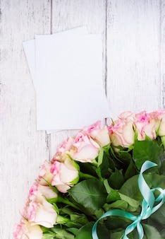 Bouquet of pink roses with blue ribbon on a vintage wooden background with papers