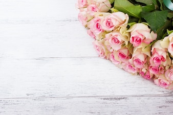 Bouquet of pink roses with blue ribbon on a vintage wooden background
