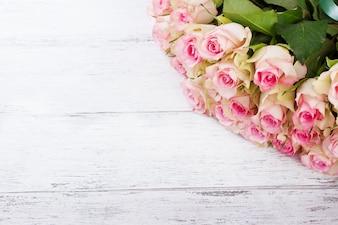 ヴィンテージの木製の背景に青いリボンとピンクのバラの花束