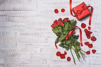 Bouquet of roses on a wooden table with a gift