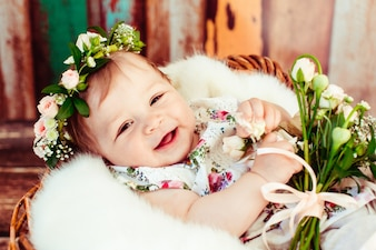 Bouquet of tiny roses lies on knees of little girl lying in the basket