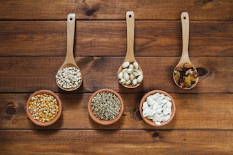 Bowls with seeds and ladles with nuts