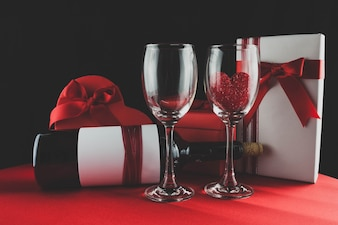 Box of chocolates with a bottle of wine and two glasses one with a heart