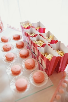 Boxes with pop-corn stand before dish with macaroons
