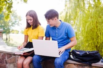 Boy and girl doing homework in park