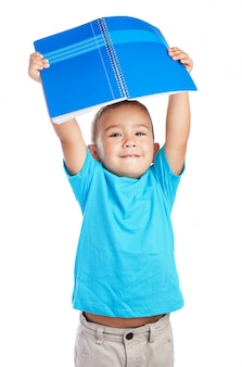 Boy holding a notebook above his head
