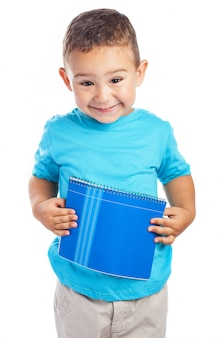 Boy holding a notebook against his belly