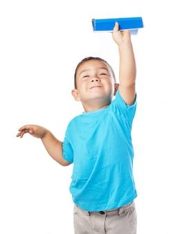 Boy holding a notebook up