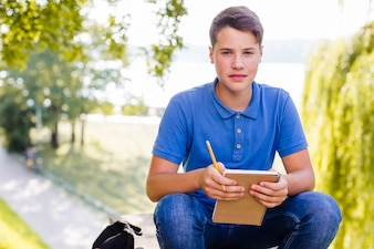 Boy holding notebook outside