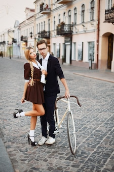 Boy hugging his girlfriend and holding a bicycle