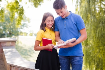Boy showing to girl book in park