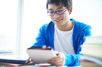 Boy sitting at desk smiling with his touchpad