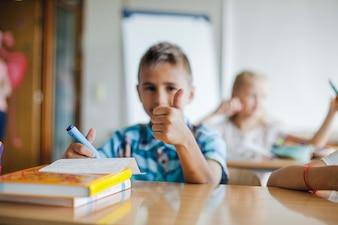 Boy sitting at school desk gesturing