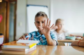 Boy sitting at school desk showing palm