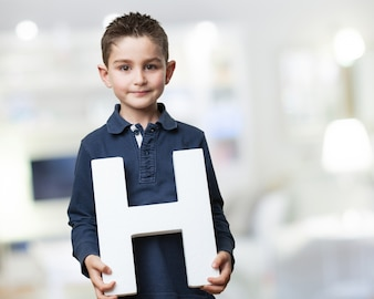 Boy smiling while holding the letter  h
