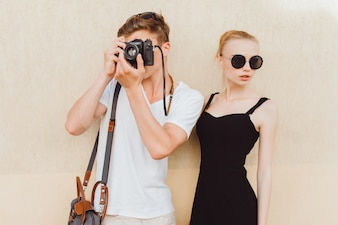 Boy taking a photo while a girl poses beside him