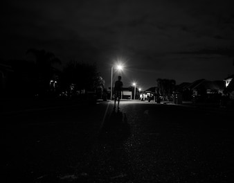 Boy walking alone at night under the street lights