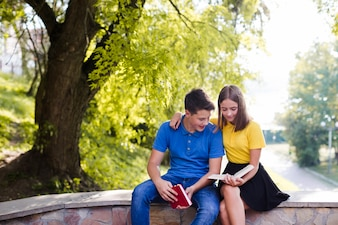 Boy with girl reading book in park
