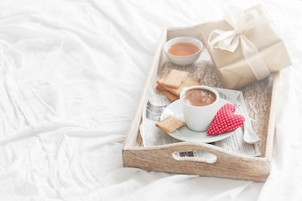 Breakfast tray with a coffee, a heart and a golden gift