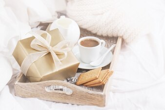 Breakfast tray with coffee, biscuits and a golden gift