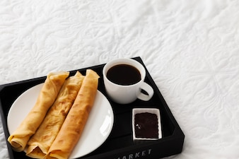 Breakfast tray with coffee, pancakes and syrup