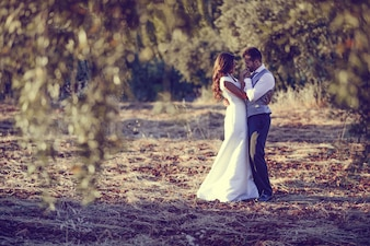 Bridal couple hugging in the field