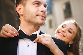 Bride adjusting her boyfriend's bow tie