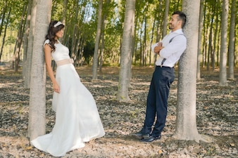 Bride and groom exchange glances in the field